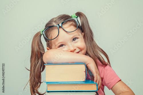 Fototapeta smiling beautiful cute little girl leaning on thick books