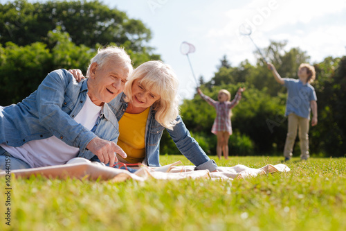 Happy grandparents looking downwards at magazine