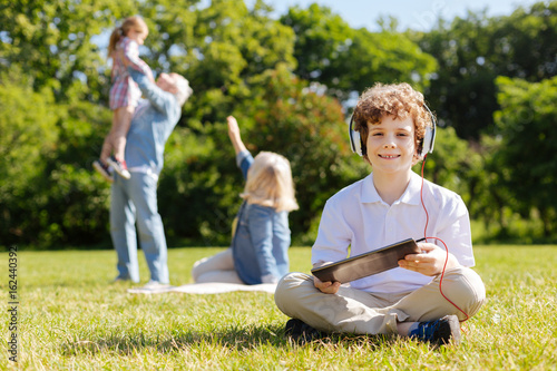 Positive boy crossing legs while sitting on the grass