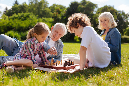 Kind grandpa helping his granddaughter play chess