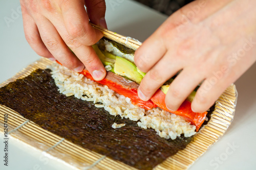 Preparation of healthy sushi rolls with brown rice and salmon. Hands chef chef.