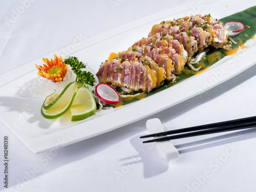 Dish of cooked tuna fish sushi-style with sticks