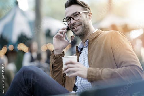 Trendy guy at Bryant park using smartphone