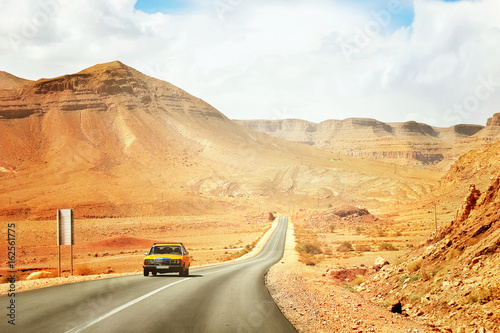 The yellow taxi rides along the mountain road in the Mid Atlas Mountains. Africa. Morocco.