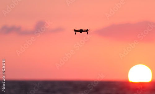 Drone flies over a colourful sunrise sky.