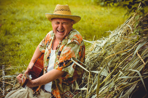 Plakát Funny older man in print shirt tourist playing guitar and sing song on nature ou