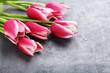 Bouquet of pink tulips on grey wooden table