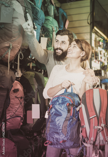 joyous couple examining rucksacks in sports equipment store Poster
