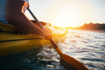 Close up of man holding kayak paddle at sunset