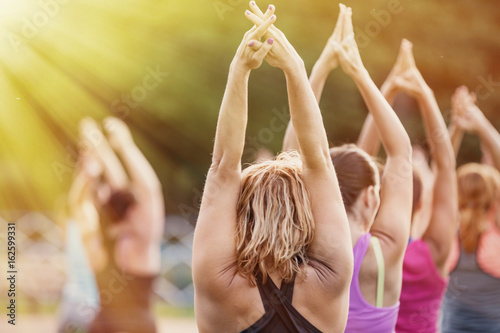 Group of women practicing yoga together during a beautiful sunny day on the meadow