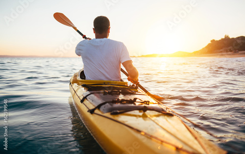 Tylni widok kayaker mężczyzna paddle kajak przy zmierzchu morzem