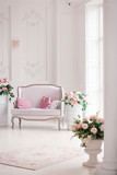 Interior of a snow-white living room with a vintage sofa and flowers - 162600728