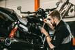 Professional mechanic working screwdriver and motorcycle repairs. Handsome young man repairing motorcycle in repair shop.
