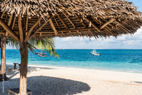 beautiful colorful view of blue ocean from beach with straw umbrella Poster