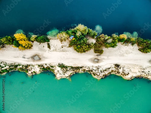 Fotobehang Groen blauw Aerial view - narrow strip of sandy shore and green and blue water, top view