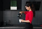 Beautiful young woman making coffee-tea in a modern kitchen  - 162618519