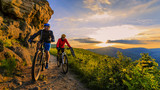 Kolarstwo górskie kobiet i mężczyzna jedzie na rowerach w górach zachód słońca krajobraz lasów. Para jeździła na torze MTB enduro. Aktywność sportowa na świeżym powietrzu.