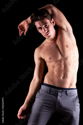 Poster Athlet in nude torso posing on black background in studio photo