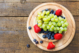Flat lay, grapes, blueberries and strawberries on wooden table - 162645575