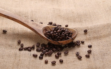 pile coffee beans and wooden spoon on jute background, texture