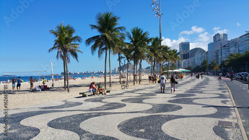 Foto Murales Copacabana, Rio de Janeiro, Brazil - June 25, 2017- Famous geometric boardwalk of Copacabana in summer day with people walking and practicing sports