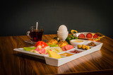 Traditional Turkish breakfast served on wooden table with dark background