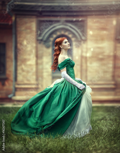 Beautiful, young, red-haired girl in a green medieval dress, climbs the stairs to the castle Poster