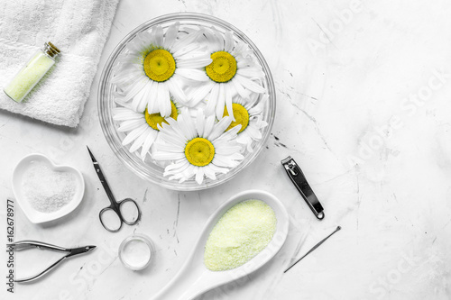 natural cosmetics with bowl of chamomiles and tools for manicure on white textural background top view space for text