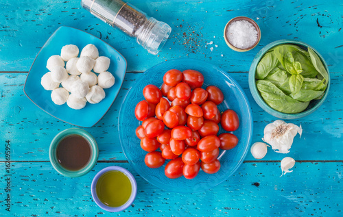 Ingredients for caprese salad on a blue table