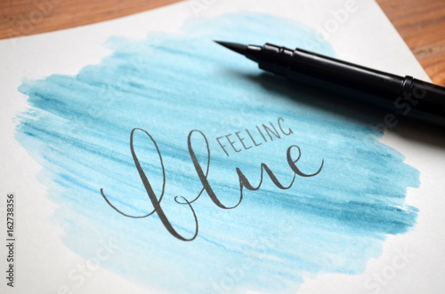 FEELING BLUE hand-lettered in notebook on blue watercolour background
