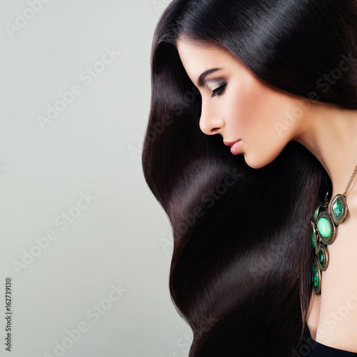 Haircare Concept. Glamorous Brunette Woman with Perfect Hairstyle and Makeup. Beautiful Model with  Long Healthy Hair, Profile