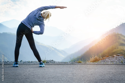 Athlete at the top of the mountain doing workout.