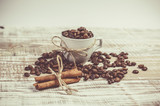 Connected cinnamon sticks and a cup with fresh coffee beans on the table