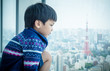 Asian boy is looking out to Tokyo city copy space