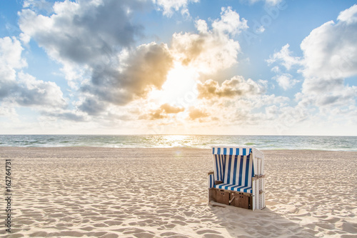 Foto auf Acrylglas See sonnenuntergang Einzelner Strandkorb bei Sonnenuntergang