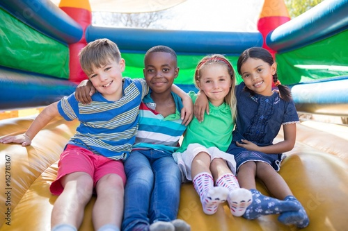 Portrait of friends with arms around sitting on bouncy castle