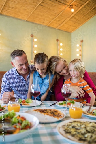 Happy family enjoying dinner at restaurant