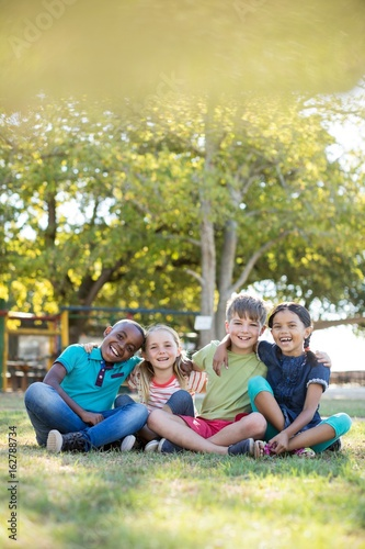 Portrait of cheerful children with arms around sitting at park