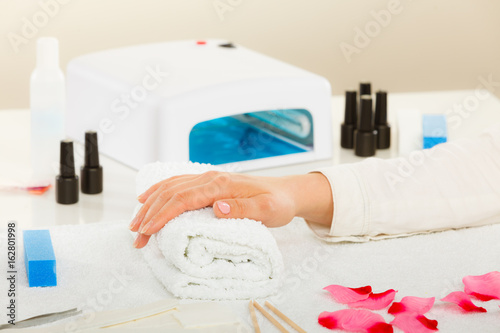 Woman hand on towel, next to manicure set