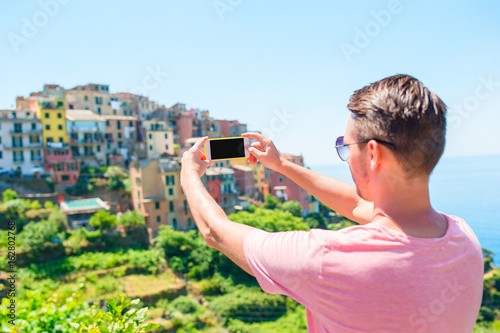 Young man taking selfie background beautiful old italian village, Cinque Terre, Liguria, Italy