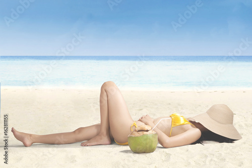 Young woman relaxing on beach with hat