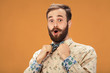 Surprised happy man with beard and moustache looking sideways in excitement, isolated on orange background