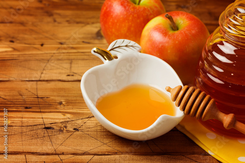 Rosh hashanah jewish new year holiday celebration concept. Honey and apples over wooden background