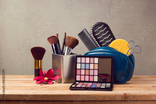 Makeup and beauty products on wooden table over gray background