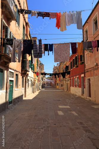 VENICE - APRIL 10, 2017: The view on alley in Venice. Laundry drying in the sun over alley in Venice Italy, on April 10, 2017 in Venice, Italy