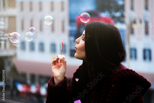 Young beautiful woman bubble blower