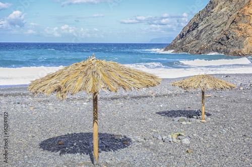 straw sunshades at a pebbly beach