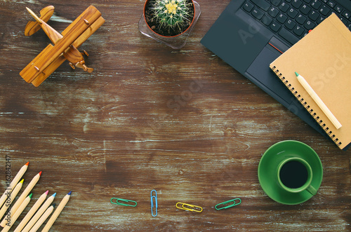Top view of office work table with leptop, notebbok and cup of coffee