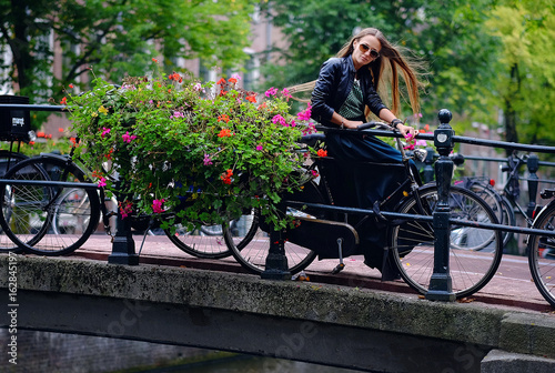 Portrait of a girl model on a city street next to a bicycle and flowers. Fashion, style, beauty.