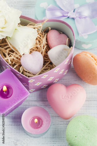 Soap, gift box and pink lit candle